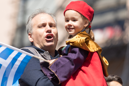 Chicago, Illinois, USA - April 29, 2018 Greek man hold his child wearing traditional clothing while the child waves the greek flag at the Greek Independence  Day Parade Standard-Bild - 106862597