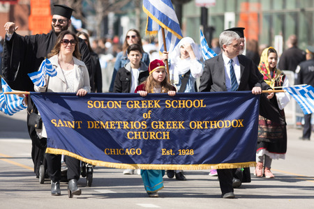 Chicago, Illinois, USA - April 29, 2018 Members of the Solon Greek School of Saint Demetrios Greek Orthodox Church wearing traditional clothing and waving greek flags at the Greek Independence  Day Parade