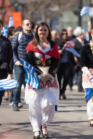 Chicago, Illinois, USA - April 29, 2018  Greek woman wearing traditional clothing waving the greek flag at the Greek Independence  Day Parade Standard-Bild - 106862613