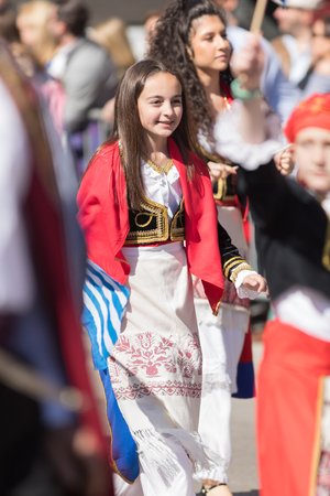 Chicago, Illinois, USA - April 29, 2018  Greek woman wearing traditional clothing waving the greek flag at the Greek Independence  Day Parade Standard-Bild - 106862614