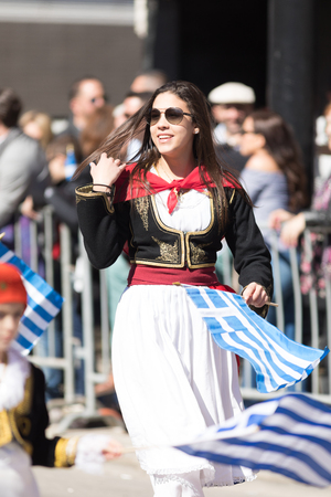 Chicago, Illinois, USA - April 29, 2018  Greek woman wearing traditional clothing waving the greek flag at the Greek Independence  Day Parade Standard-Bild - 106862616