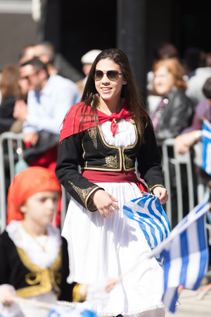 Chicago, Illinois, USA - April 29, 2018  Greek woman wearing traditional clothing waving the greek flag at the Greek Independence  Day Parade Standard-Bild - 106862617