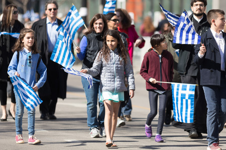 Chicago, Illinois, USA - April 29, 2018 Greek children and adults waving greek flags at the Greek Independence  Day Parade Standard-Bild - 106862619
