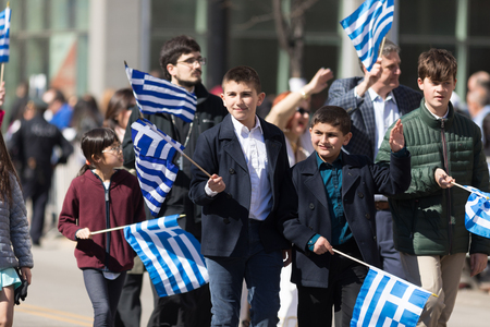 Chicago, Illinois, USA - April 29, 2018 Greek children and adults waving greek flags at the Greek Independence  Day Parade Standard-Bild - 106862620