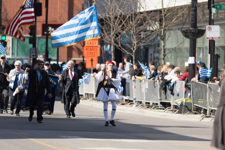 Chicago, Illinois, USA - April 29, 2018 Older greek men wearing traditional clothing carrying the american and greek flags at the Greek Independence  Day Parade Editorial