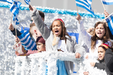 Chicago, Illinois, USA - April 29, 2018 Greek children wearing traditional clothing waving the greek at the Greek Independence  Day Parade Standard-Bild - 106862630