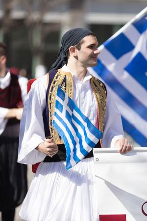 Chicago, Illinois, USA - April 29, 2018 Greek man wearing traditional clothing waving the greek flag at the  Greek Independence  Day Parade Standard-Bild - 106862652
