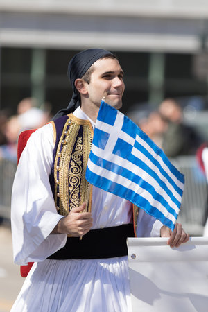 Chicago, Illinois, USA - April 29, 2018 Greek man wearing traditional clothing waving the greek flag at the  Greek Independence  Day Parade Standard-Bild - 106862653
