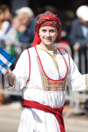 Chicago, Illinois, USA - April 29, 2018  Greek woman wearing traditional clothing waving the  greek flag at the Greek Independence  Day Parade Standard-Bild - 106862656