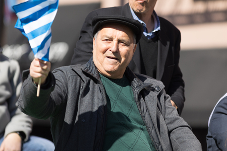 Chicago, Illinois, USA - April 29, 2018 Greek man waving the greek flag at the Greek Independence  Day Parade Editorial