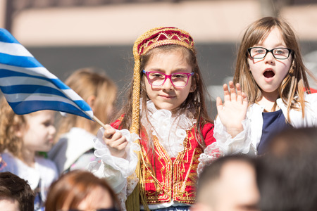 Chicago, Illinois, USA - April 29, 2018  Children wearing traditional clothing waving the greek flag at the Greek Independence  Day Parade