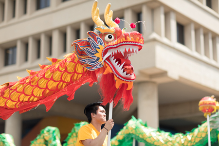 Indianapolis, Indiana, USA - May 26, 2018, Members of the Indianapolis Chinese Community Center, Inc. wearing traditional chinese clothing and holding dragons at the Indy 500 Parade