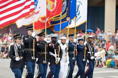 Indianápolis, Indiana, Estados Unidos - 26 de mayo de 2018, miembros de las Fuerzas Armadas de los Estados Unidos portando la bandera estadounidense marchando por la calle durante el Desfile de Indy 500