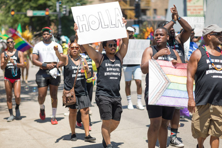 Chicago, Illinois, USA - June 24, 2018 People wearing shirts that say, black men loving black men is a revolutionary act. Joseph Beam  celebrating during the LGBTQ Pride Parade in Chicago Editorial
