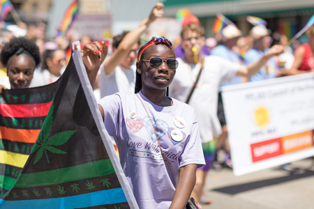 Chicago, Illinois, USA - June 24, 2018 People waving rainbow flags celebrating during the LGBTQ Pride Parade in Chicago