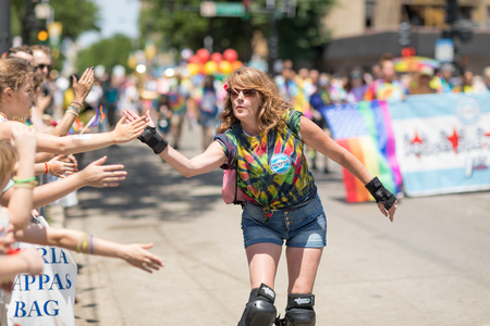 Chicago, Illinois, USA - June 24, 2018 Woman on roller skates giving the spectaors high fives during the LGBTQ Pride Parade in Chicago