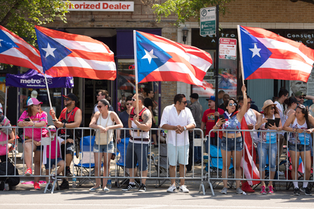 Chicago, Illinois, USA - June 16, 2018 A group of spectators wave the Puerto Rican flag during the Puerto Rican People's Parade 에디토리얼