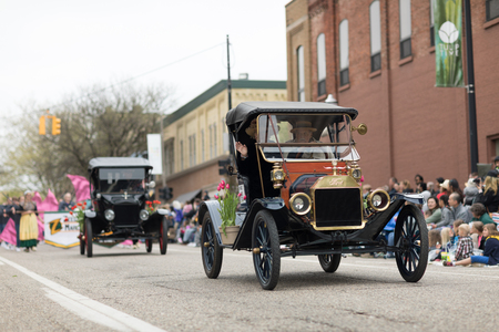 Holland, Michigan, USA - May 12, 2018 Ford Model T, with tulip flowers, driven by men wearing retro clothing, drive down the road at the Muziek Parade, during the Tulip Time Festival