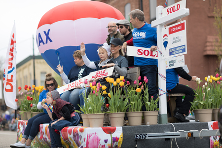 Holland, Michigan, USA - May 12, 2018 Float promoting Re/Max  with a hot air balloon and people holding signs that say, sold, sale pending at the Muziek Parade, during the Tulip Time Festival
