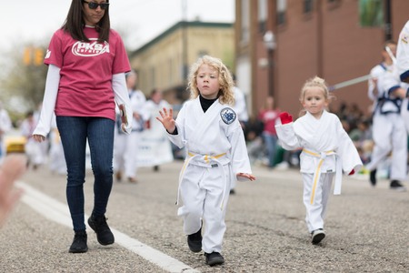 Holland, Michigan, USA - May 12, 2018 Children members of PKSA Karate walk down the road at the Muziek Parade, during the Tulip Time Festival