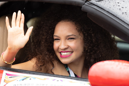 Peru, Indiana, USA - July 21, 2018 Young african american woman waves and smile at the camera at the Circus City Festival Parade