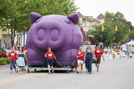 Frankenmuth, Michigan, USA - June 10, 2018 Men and women pulling a giant balloon in shape of a pig down the road at the Bavarian Festival Parade. Editöryel