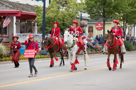 Frankenmuth, Michigan, USA - June 10, 2018 Women wearing red outfits from the Harmony Acres Arabians ridding horses down the road at the Bavarian Festival Parade. Editöryel