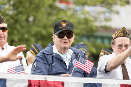 Frankenmuth, Michigan, USA - June 10, 2018 Military Veterans from Frankenmuth riding on top of a trailer holding american flags at the Bavarian Festival Parade. Editöryel