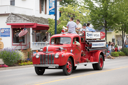 Frankenmuth, Michigan, USA - June 10, 2018 Men riding on the back of a classic firetruck playing music instruments going down the road at the Bavarian Festival Parade.