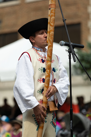 Whiting, Indiana, USA - July 28, 2018 Man wearing traditional slovak clothing plays the Fujara traditional musical instrument at the Pierogi Fest