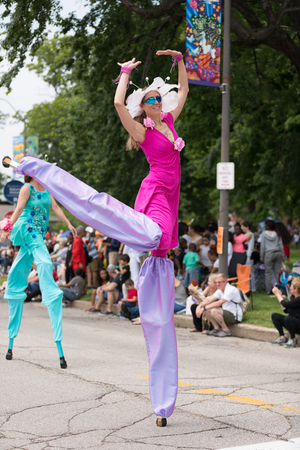 Cleveland, Ohio, USA - June 9, 2018 woman on stilts dress up as a flower At the abstract art festival Parade The Circle Editorial