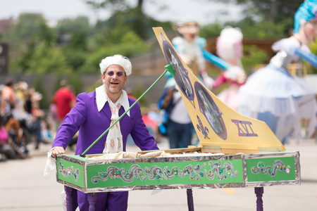 Cleveland, Ohio, USA - June 9, 2018 man pretends to play the piano wearing a white wig and purple glasses At the abstract art festival Parade The Circle Editorial