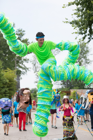 Cleveland, Ohio, USA - June 9, 2018 man wearing a green outfit dancing on stilts At the abstract art festival Parade The Circle Editorial