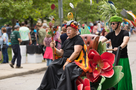 Cleveland, Ohio, USA - June 9, 2018 man dress up as a bug on a chair with flowers being pushed down the road At the abstract art festival Parade The Circle Editorial