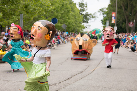 Cleveland, Ohio, USA - June 9, 2018 men and women dancing wearing a large abstract mask and wearing traditional mexican clothing At the abstract art festival Parade The Circle Redactioneel