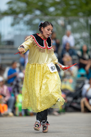 Milwaukee, Wisconsin, USA - September 8, 2018 The Indian Summer Festival, Young woman wearing traditional native american clothing, dancing at the pow wow competition. 新聞圖片