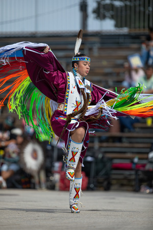 Milwaukee, Wisconsin, USA - September 8, 2018 The Indian Summer Festival, Young woman wearing traditional native american clothing, dancing at the pow wow competition. Editorial