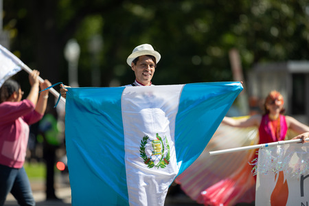 Washington, D.C., USA - September 29, 2018: The Fiesta DC Parade, Man wearing traditional clothing carrying the flag of Guatemala 報道画像