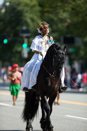 Washington, D.C., USA - September 29, 2018: The Fiesta DC Parade, Woman wearing traditional Panamanian clothing riding a horse