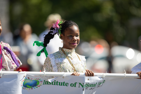 Washington, D.C., USA - September 29, 2018: The Fiesta DC Parade, Young women wearing traditional clothing from panama carrying a banner promoting the Institute of National Dance