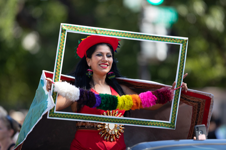 Washington, D.C., USA - September 29, 2018: The Fiesta DC Parade, Peruvian woman wearing traditional clothing holding a frame poses for the camera Editorial