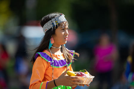 Washington, D.C., USA - September 29, 2018: The Fiesta DC Parade, peruvian girl wearing traditional clothing walking down the street carrying friut