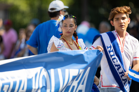 Washington, D.C., USA - September 29, 2018: The Fiesta DC Parade, Woman wearing traditional clothing from Nicaragua going down the street 報道画像