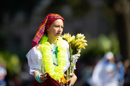 Washington, D.C., USA - September 29, 2018: The Fiesta DC Parade, Woman from El Salvador wearing traditional clothing carrying flowers 報道画像