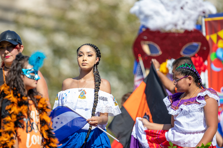 Washington, D.C., USA - September 29, 2018: The Fiesta DC Parade, Woman from Honduras waving the national flag and wearing traditional clothing
