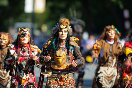 Washington, D.C., USA - September 29, 2018: The Fiesta DC Parade, Men and women from guatemala wearing traditional clothing representing the Indigenous peoples of guatemala wearing abstract mask in sh