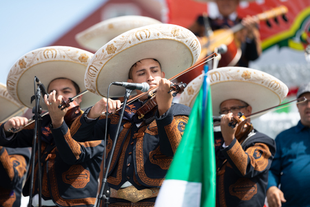 Chicago, Illinois , USA - September 9, 2018 The 26th Street Mexican Independence Parade, mexican men wearing traditional mariachi clothing playing the Violin