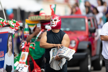 Chicago, Illinois , USA - September 9, 2018 The 26th Street Mexican Independence Parade, mexican man wearing a luchador mask giving away newspapers Editorial