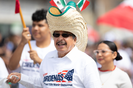 Chicago, Illinois , USA - September 9, 2018 The 26th Street Mexican Independence , man wearing a big sombrero with mexican flags on it, promoting the democrat George Cardenas 写真素材 - 116749534
