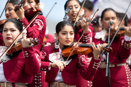 Chicago, Illinois , USA - September 9, 2018 The 26th Street Mexican Independence Parade, Mexican women wearing traditional mariachi clothing playing the violin Editorial